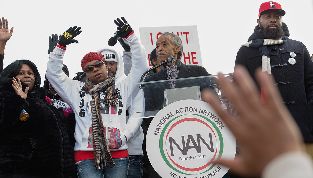 ". (L-R) Samaira Rice, the mother of Tamir Rice; Lesley McSpadden, the mother of Michael Brown Jr; Rev. Al Sharpton and Michael Brown Sr., the father of Michael Brown Jr, raise their hands in the air during the ""Justice For All\"" march and rally through the nation\'s capital December 13, 2014 in Washington, DC. Organized by Sharpton\'s National Action Network, this march and others like it across the country aim to tell Congress and the country that demonstrators will not stand down until there is systemic change, accountability and justice in cases of police misconduct. Sharpton said the demonstration is happening in Washington \""because all over the country we all need to come together and demand this Congress deal with the issues, that we need laws to protect the citizens in these states from these state grand jurors.\""  (Photo by Chip Somodevilla/Getty Images)"
