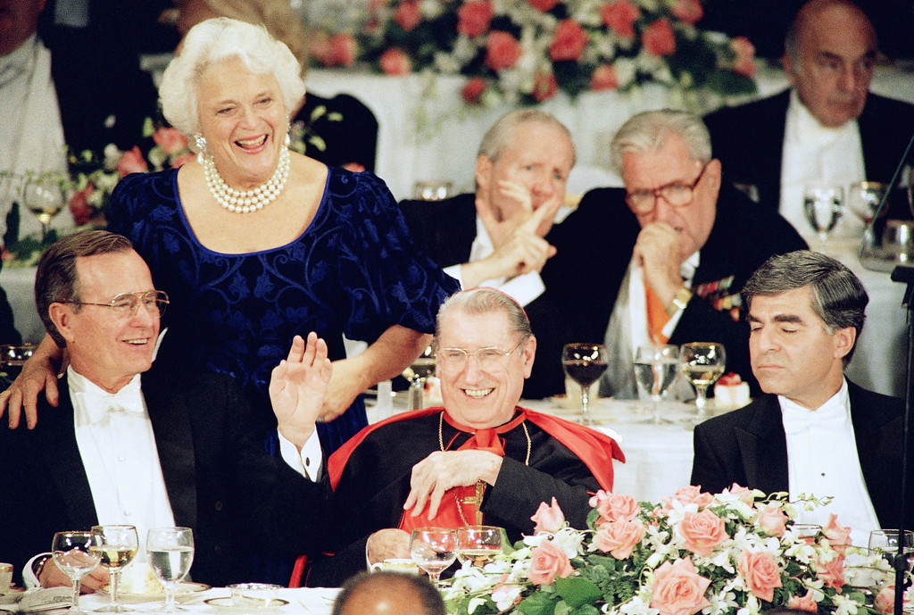 . The Republican and Democratic candidates for president appear with New York?s Cardinal John J. O?Connor at the annual Alfred E. Smith dinner on Thursday, Oct. 21, 1988 in New York.   Barbara Bush embraces her husband George Bush on the podium as she greets other guests.   From left are: George H.W.  Bush, Cardinal O?Connor, Michael Dukakis, New York Mayor Edward Koch and New Jersey Governor Thomas Kean. (AP Photo/Barry Thumma)