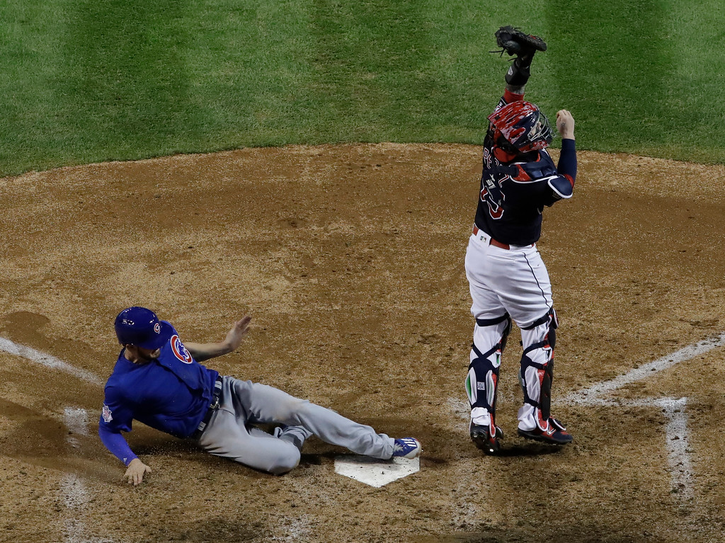 . Chicago Cubs\' Kris Bryant scores past Cleveland Indians catcher Roberto Perez during the fifth inning of Game 7 of the Major League Baseball World Series Wednesday, Nov. 2, 2016, in Cleveland. (AP Photo/David J. Phillip)