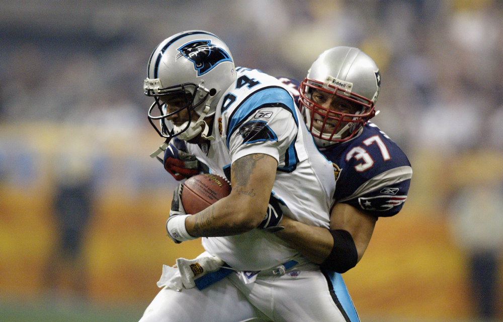 Description of . Tight end Jermaine Wiggins #84 of the Carolina Panthers is tackled by Rodney Harrison #37 of the New England Patriots during Super Bowl XXXVIII at Reliant Stadium on February 1, 2004 in Houston, Texas. The Patriots won 32-29 to claim their second Super Bowl in three years. (Photo by Donald Miralle/Getty Images)