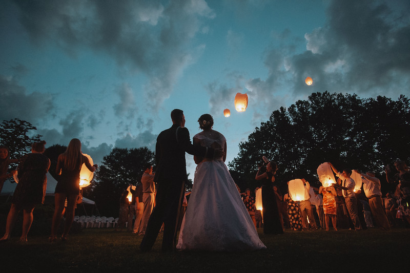 The bride and groom watch lanterns as they float into the cool evening sky.