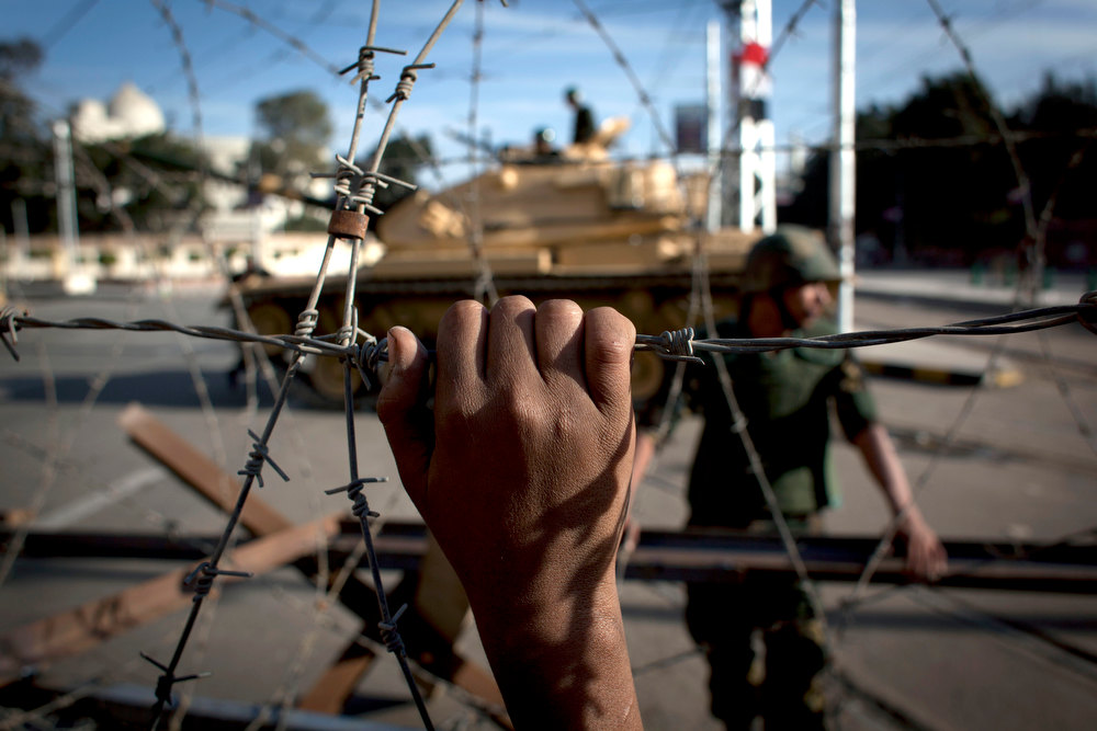 . An Egyptian army tank is seen behind barbed wire securing the perimeter of the presidential palace while protesters on the other side chant anti President Mohammed Morsi slogans, in Cairo, Egypt, Thursday, Dec. 6, 2012. The Egyptian army deployed tanks and gave both supporters and opponents of Mohammed Morsi a deadline to leave the area outside the presidential palace Thursday following fierce street battles that left several people dead and hundreds injured in the worst outbreak of violence between the two sides since the Islamist leaderís election. (AP Photo/Nasser Nasser)