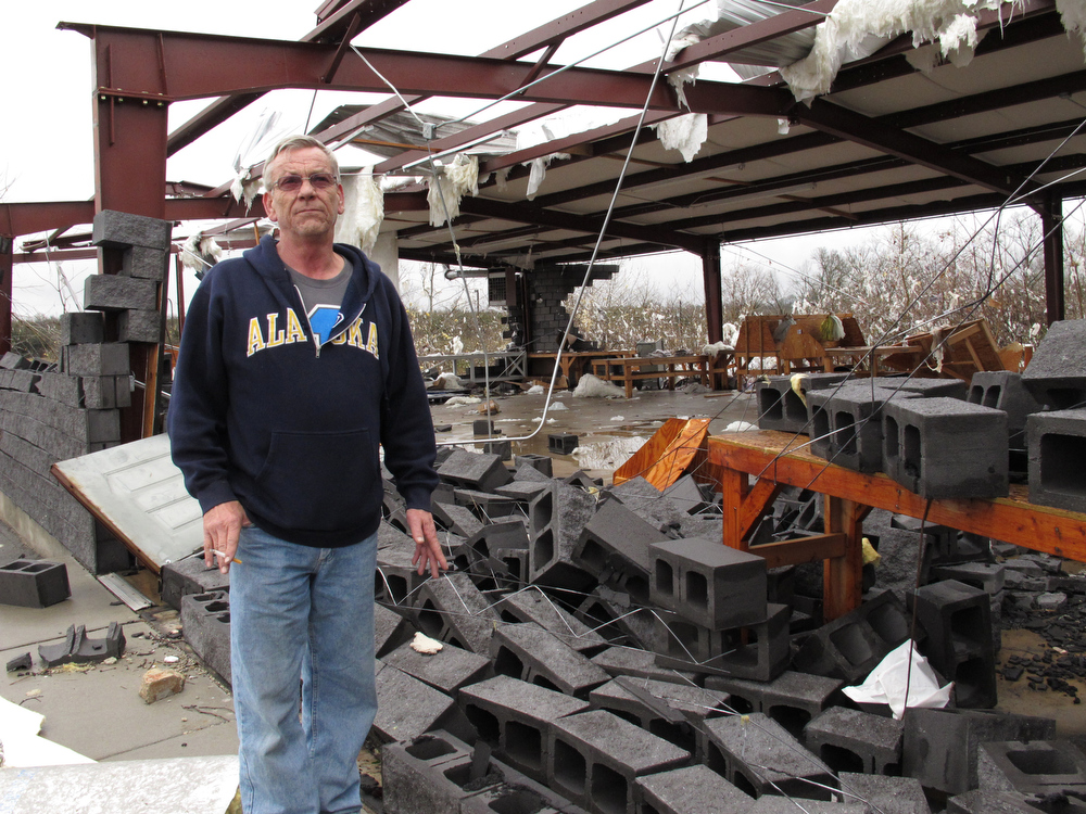 . Rick Martin stands in front of a Tennessean newspaper distribution center in Mount Juliet, Tenn., on Wednesday, Jan. 30, 2013, that was destroyed in a severe storm. Forecasters examined the damage path of 4.6 miles Wednesday morning and estimated the peak wind speed at 115 mph, qualifying the tornado as an EF-2 twister. The path of damage was about 150 yards wide. (AP Photo/Kristin M. Hall)