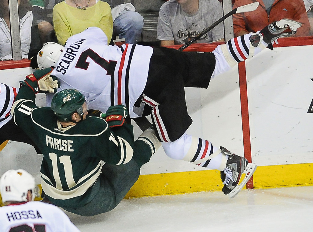 . Minnesota\'s Zach Parise and Chicago\'s Brent Seabrook fall to the ice after a check during the second period.  (Pioneer Press: Ben Garvin)