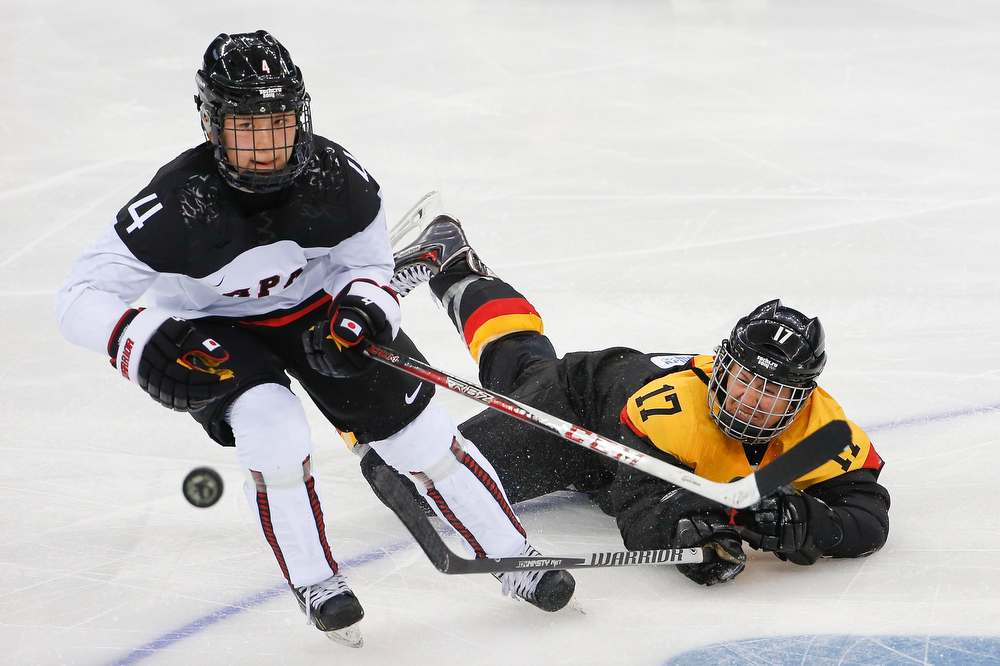 . Ayaka Toko of Japan takes control of the puck from Sara Seiler of Germany during the second period of the 2014 Winter Olympics women\'s ice hockey game at Shayba Arena, Tuesday, Feb. 18, 2014, in Sochi, Russia. (AP Photo/Petr David Josek)