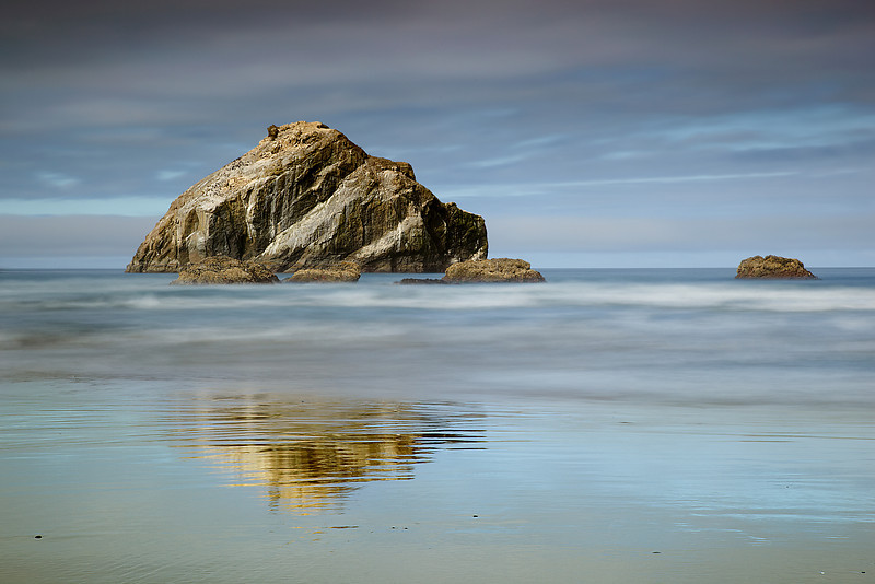 Face Rock is the famous icon of Bandon State Beach in Souther Oregon.  It sits amongst many wildly shaped sea stacks on an outstanding wide sandy beach.  To capture this scene, I waited for the sun to glance across the face at a slight angle at about 10am.  Usually this is not a great time of day for dramatic light on the landscape but with dark clouds behind, a hole opened in the clouds and illuminted the rock and beach for just a few minutes.