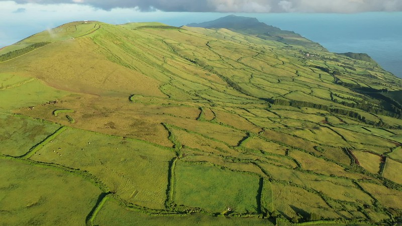 Available in 4K - Early morning landscape view on the green fields at the north coast of the Azores island of Sao Jorge, as seen from the central mountains near Pico de Esperanca.