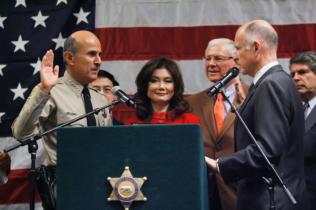 . Los Angeles County Sheriff Leroy Baca, left, is sworn into office by Governor Elect Jerry Brown at Our Lady of the Angels in Los Angeles Monday.  At center is Lee Baca\'s wife Carol.  County supervisors Mike Antonovich and Zev Yaroslavsky are in background.   12/20/2010. Photo by David Crane/Los Angeles Daily News