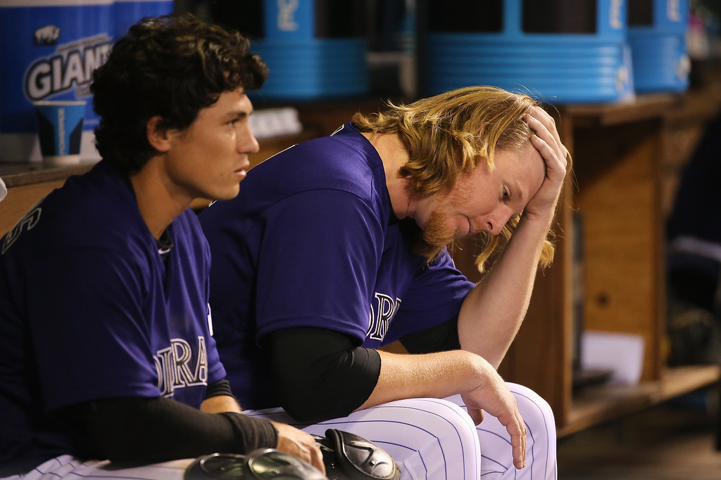 . DENVER, CO - APRIL 22:  Starting pitcher Jon Gray #55 of the Colorado Rockies sits on the dugout bench with cathcer Tony Wolters #14 after Gray was removed from the game against the Los Angeles Dodgers after the fifth inning at Coors Field on April 22, 2016 in Denver, Colorado.  (Photo by Doug Pensinger/Getty Images)