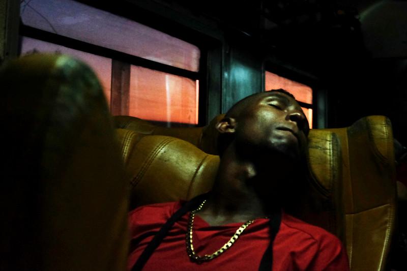A man sleeps on the train ride from Havana to Santiago de Cuba as the sun rises near Camagüey, Cuba.