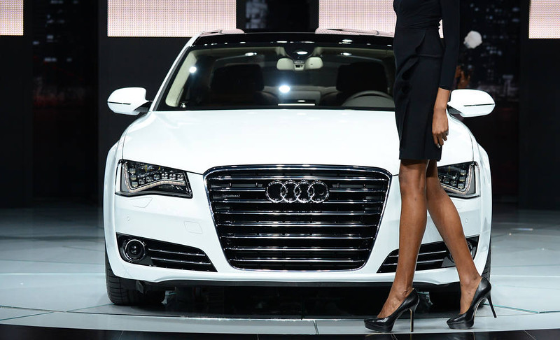 . A model walks past an Audi A8L TDI displayed on media preview day at the Los Angeles Auto Show on November 28, 2012 in Los Angeles, California. The show opens to the public from November 30 to December 9. AFP PHOTO / Frederic J.  BROWN/AFP/Getty Images