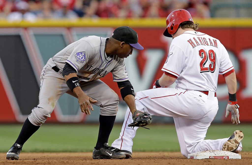 . Cincinnati Reds\' Ryan Hanigan, right, is safe at second with a double as Colorado Rockies shortstop Jonathan Herrera, left, is late with the tag in the fourth inning of a baseball game, Tuesday, June 4, 2013, in Cincinnati. (AP Photo/Al Behrman)
