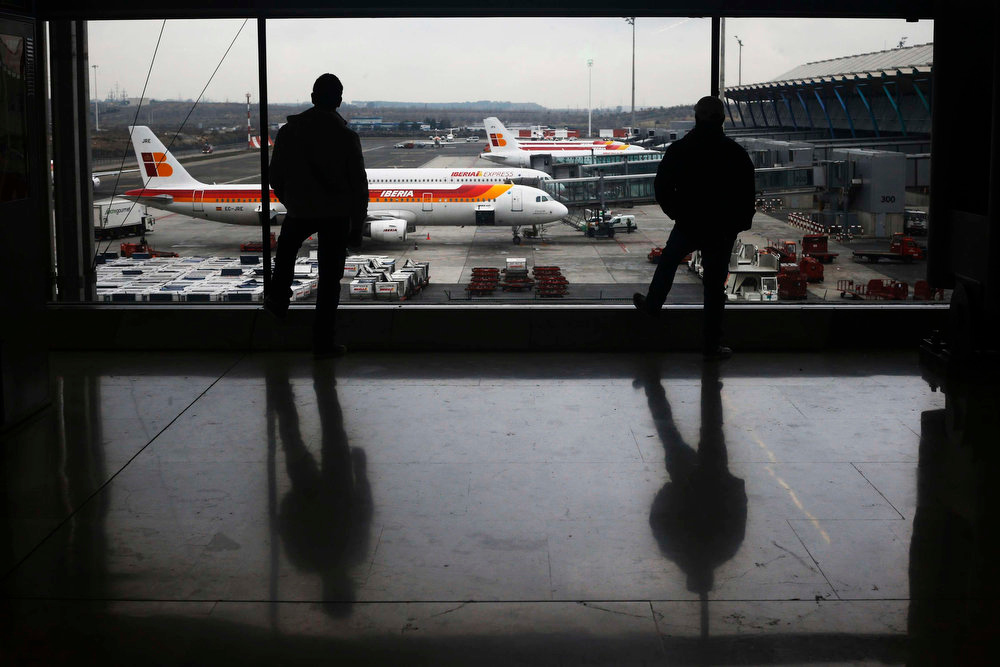 Description of . Men look at Iberia planes parked on the tarmac at Madrid's Barajas airport February 18, 2013. Workers at loss-making Spanish flag carrier Iberia will begin a five-day strike at midnight on Monday, grounding over 1,000 flights and costing the airline and struggling national economy millions of euros. REUTERS/Susana Vera