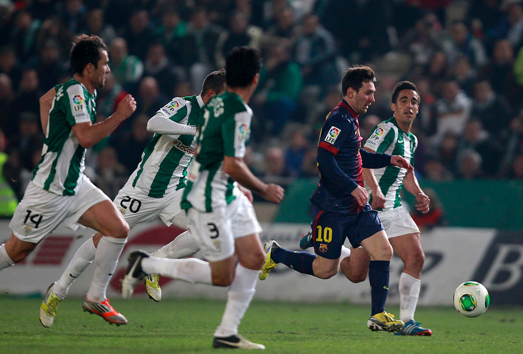 . Barcelona\'s Lionel Messi (2nd R) is chased by Cordoba\'s players during their Spanish King\'s Cup soccer match at Nuevo Arcangel stadium in Cordoba December 12, 2012. REUTERS/Marcelo del Pozo