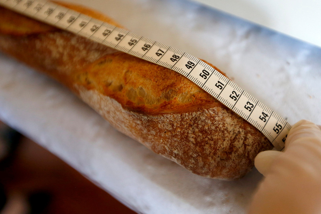 . An assistant measures a baguette registered in the competition for the \'Grand Prix de la Baguette de la Ville de Paris\' (Best Baguette of Paris 2013) annual prize at the Chambre Professionnelle des Artisans Boulangers Patissiers in Paris April 25, 2013. The baguette is a French cultural symbol par excellence and the competition saw 203 Parisian bakers who compete for recognition as finest purveyor of one of France\'s most iconic staples. The baguettes are registered, given anonymous white wrappings and an identification number. They are then carefully weighed and measured to ensure they do not violate the contest\'s strict rules. 52 entries were withdrawn for failing to measure between 55-70cm long or not matching the acceptable weight of between 250-300g. Every year, the winner earns the privilege of baking bread for the French President.   REUTERS/Charles Platiau