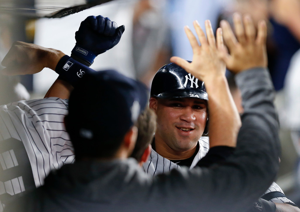 . New York Yankees\' Gary Sanchez is congratulated by teammates in the dugout after hitting a solo home run against the Cleveland Indians during the sixth inning in Game 4 of baseball\'s American League Division Series, Monday, Oct. 9, 2017, in New York. (AP Photo/Kathy Willens)