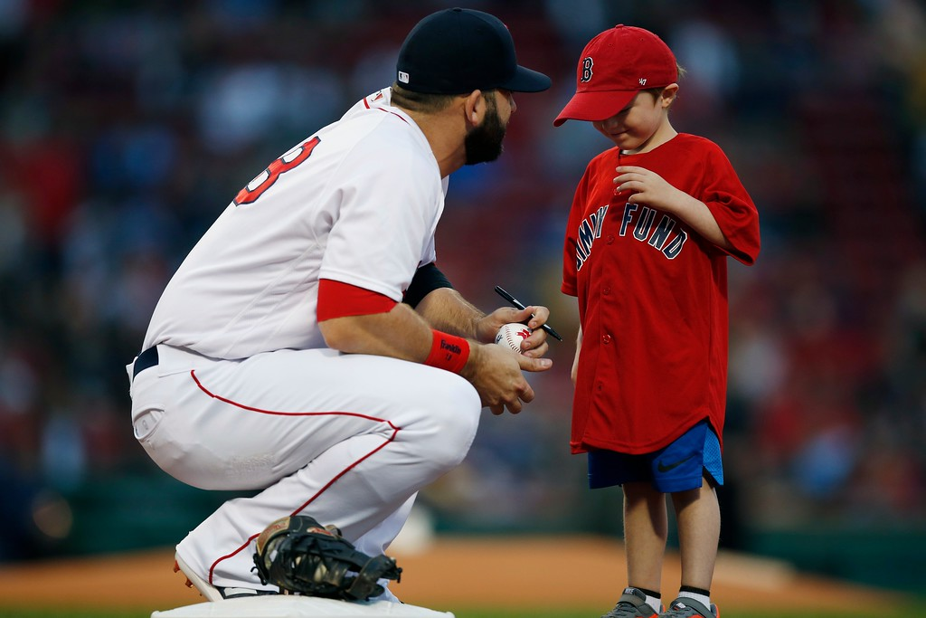 . Boston Red Sox\'s Mitch Moreland talks to a young cancer patient before a baseball game against the Cleveland Indians in Boston, Tuesday, Aug. 21, 2018. (AP Photo/Michael Dwyer)