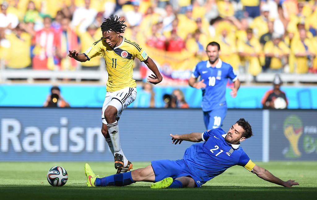. Colombia\'s midfielder Juan Guillermo Cuadrado (L) vies with Greece\'s midfielder Kostas Katsouranis (R) during a Group C football match between Colombia and Greece at the Mineirao Arena in Belo Horizonte during the 2014 FIFA World Cup on June 14, 2014.   AFP PHOTO / EITAN ABRAMOVICH