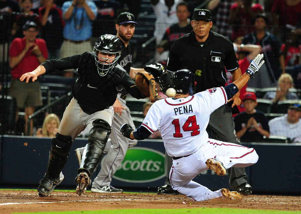 . ATLANTA, GA - MAY 23: Ramiro Pena #14 of the Atlanta Braves scores the go-ahead run in the 8th inning against Jordan Pacheco #58 of the Colorado Rockies at Turner Field on May 23, 2014 in Atlanta, Georgia. (Photo by Scott Cunningham/Getty Images)