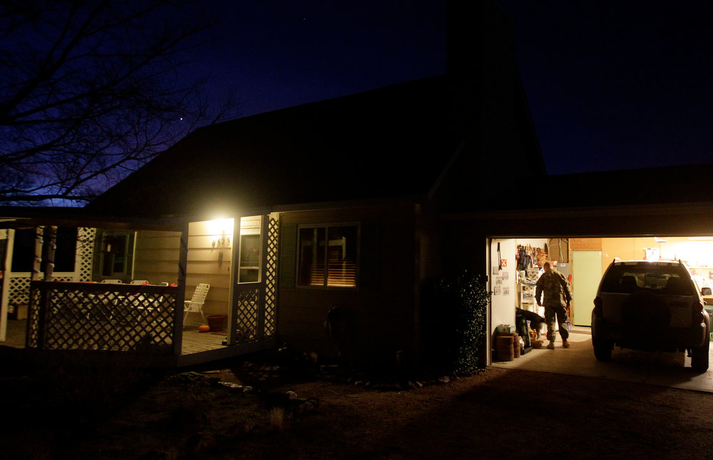 . In this Nov. 30, 2012 file photo, 1st Lt. Aaron Dunn enters his home before sunrise on the morning of his return from a deployment in Afghanistan, in Fountain, Colo. Many soldiers returning home after long deployments describe the change as welcome, but also overwhelming at first. (AP Photo/Brennan Linsley)