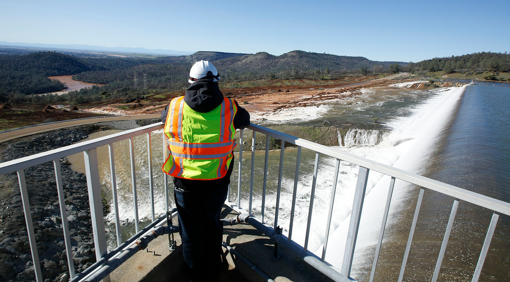 . A employee of the Department of Water Resources watches as water flows over the emergency spillway at Oroville Dam Saturday, Feb. 11, 2017, in Oroville, Calif. Water started flowing over the spillway, at the nation\'s tallest dam, for the first time Saturday morning after erosion damaged the Northern California dam\'s main spillway.(AP Photo/Rich Pedroncelli)