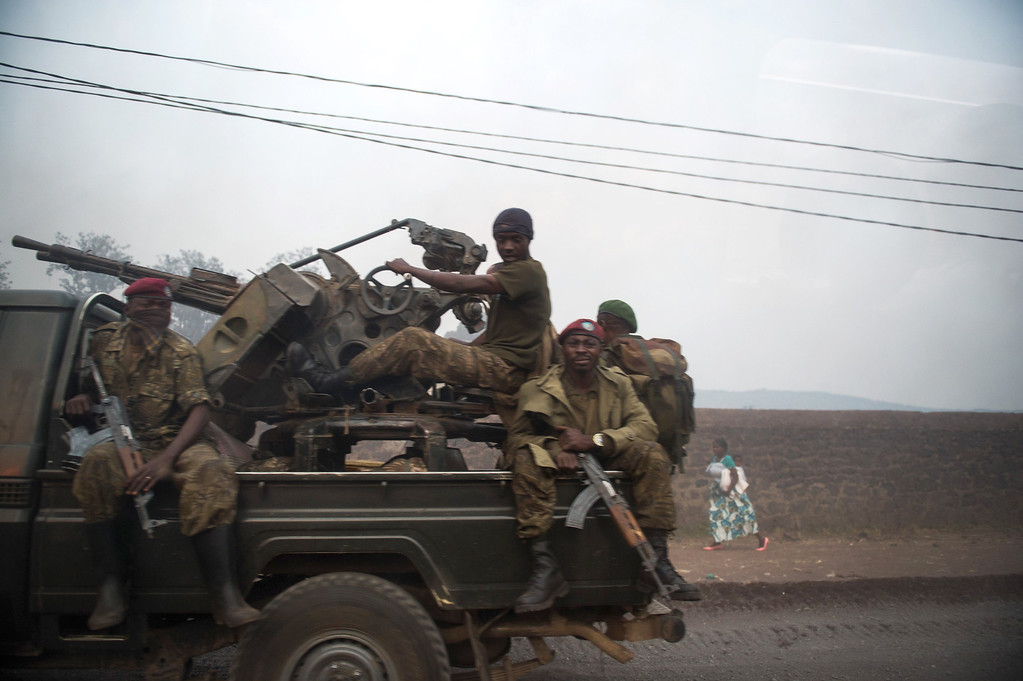 . Photo taken through a car window shows a group of Congolese army soldiers driving out of Goma in the east of the Democratic Republic of the Congo on July 14, 2013. Exchanges of artillery and rocket-fire broke out today between the Congolese army and M23 rebels, with impact visible from Kanyarucinya in the foot-hills of the Nyiragonga volcano. More than 55,000 refugees from eastern Democratic Republic of Congo have arrived in Uganda after fleeing a rebel attack, Red Cross officials said July 14, although the rate of new arrivals has begun to slow down. PHIL MOORE/AFP/Getty Images