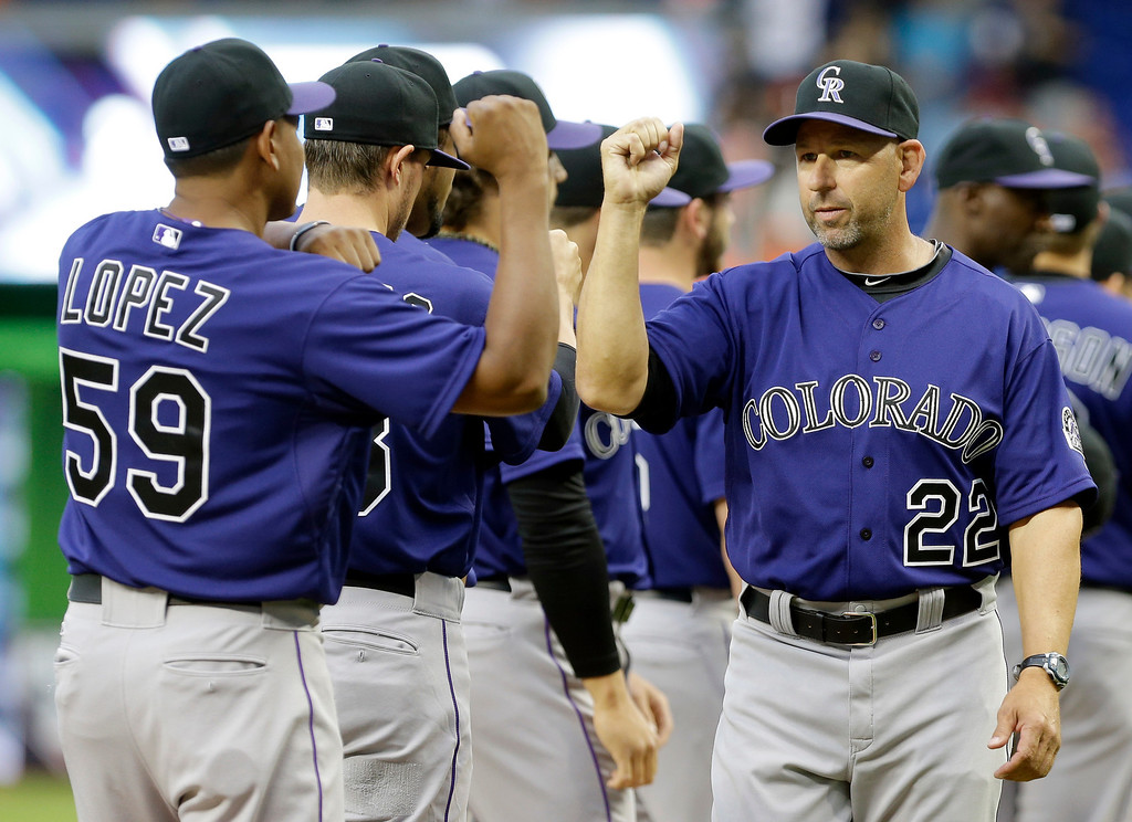 . Colorado Rockies manager Walt Weiss (22) high-fives relief pitcher Wilton Lopez (59) before an opening day baseball game against the Miami Marlins, Monday, March 31, 2014, in Miami. (AP Photo/Lynne Sladky)
