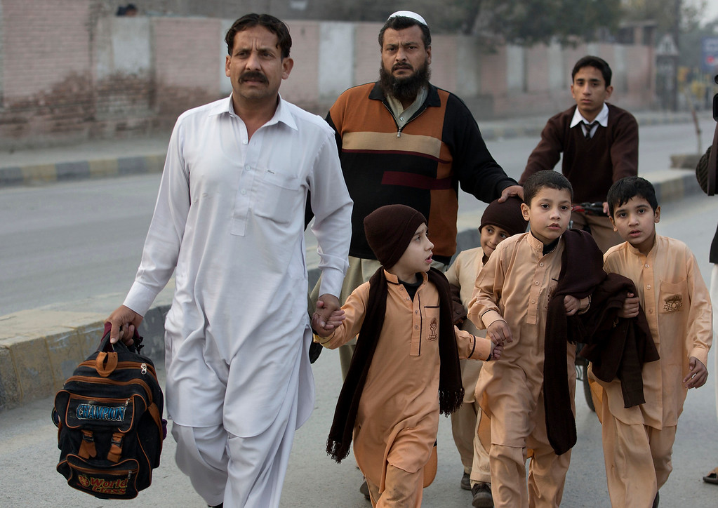 . Pakistani parents escort their children outside a school attacked by the Taliban in Peshawar, Pakistan, Tuesday,  Tuesday, Dec. 16, 2014. Taliban gunmen stormed a military-run school in the northwestern Pakistani city of Peshawar on Tuesday, killing and wounding scores, officials said, in the highest-profile militant attack to hit the troubled region in months. (AP Photo/B.K. Bangash)