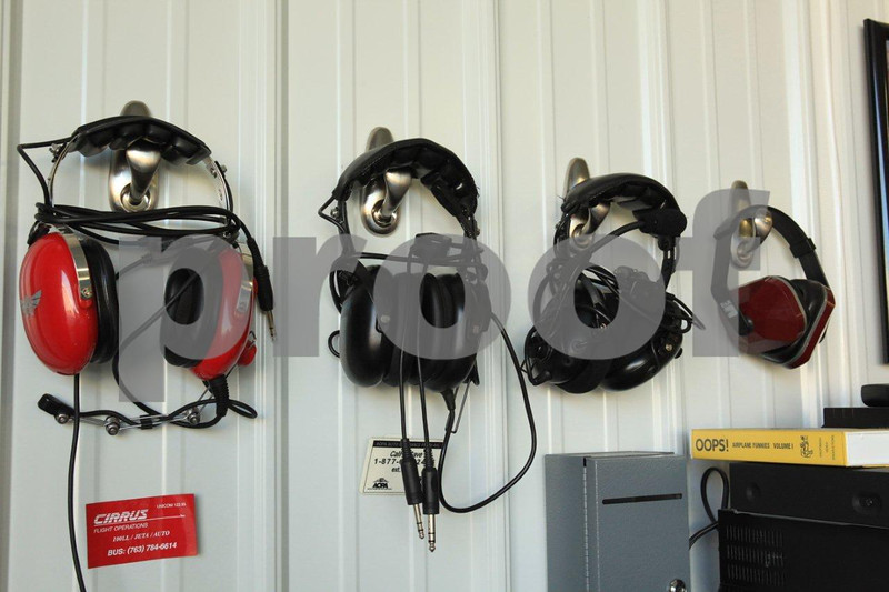 Headsets hanging on the wall in the hanger  ready for use by civilian pilots.