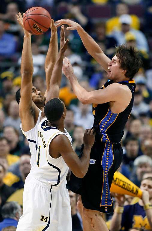 . South Dakota State forward Jordan Dykstra, right, passes the ball against Michigan forwards Jon Horford, left rear, and Glenn Robinson III during the first half of a second-round game of the NCAA men\'s college basketball tournament Thursday, March 21, 2013, in Auburn Hills, Mich. (AP Photo/Duane Burleson)