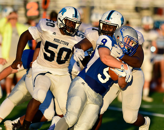 9/14/2018 Mike Orazzi | Staff Bristol Eastern High School's Matt DAmato (9) and Middletown's Osbourne Richards (50) and Nygell Smikle (77) during Friday night's football game with Middletown in Bristol.