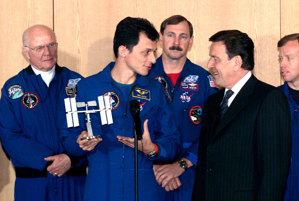. German Chancellor Gerhard Schroeder, right, receives a model of the future multi-nation space station from crew member of the NASA Space-Shuttle-Mission STS 95 astronaute, Spaniard Pedro Duque of the ESA, left, during a reception in Bonn Tuesday January 19, 1999. In background the U.S. astronauts John Glenn, commander Curtis L. Brown and Steven Lindsey, from left, watch the scene. (AP Photo/Roberto Pfeil)