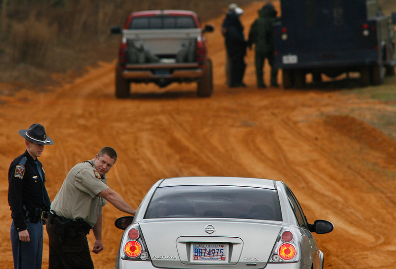 . As bomb squad personnel (in back) prepare to enter the scene, law enforcement officials turn back a vehicle at a roadblock near a standoff with the shooter in Midland City, Alabama January 30, 2013. A standoff continued on Wednesday with a gunman who boarded an Alabama school bus and fatally shot the driver before fleeing with a young child and holing up in an underground bunker, authorities said.  REUTERS/Phil Sears