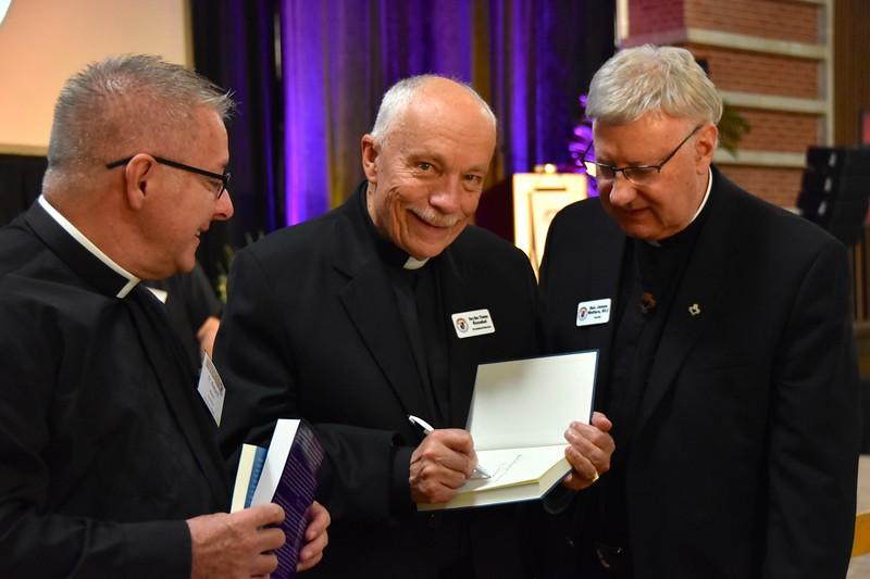 Fr. Tom Knoebel signs his recent book