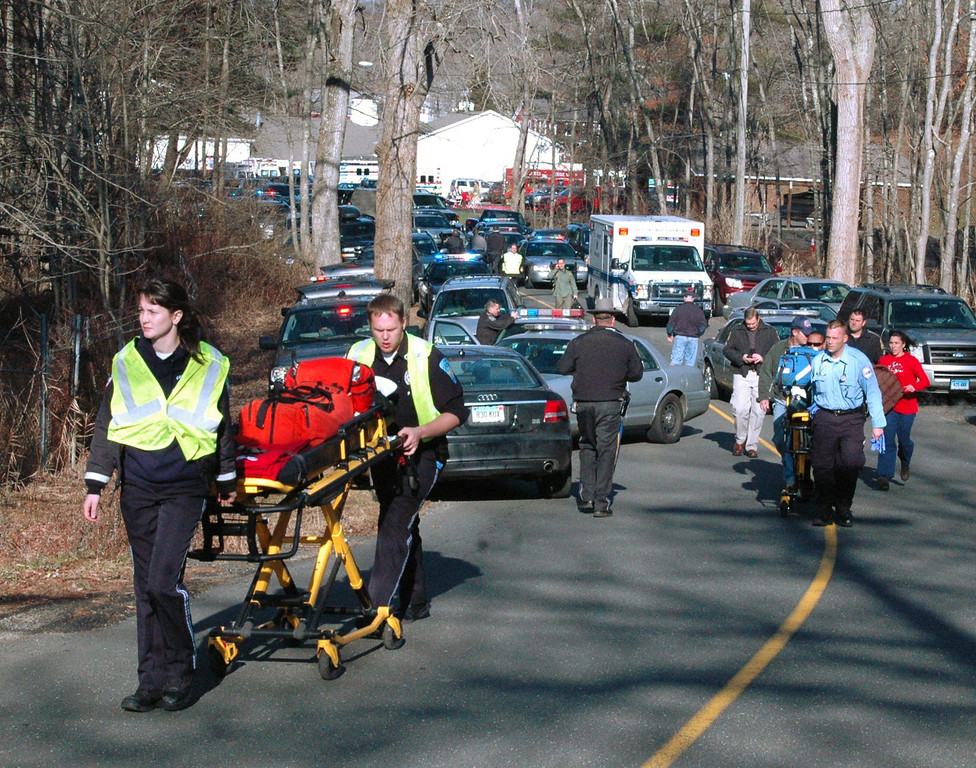 . In this photo provided by the Newtown Bee, paramedics push stretchers toward Sandy Hook Elementary School in Newtown, Conn., where authorities say a gunman opened fire, killing 26 people, including 20 children, Friday, Dec. 14, 2012. (AP Photo/Newtown Bee, Shannon Hicks)