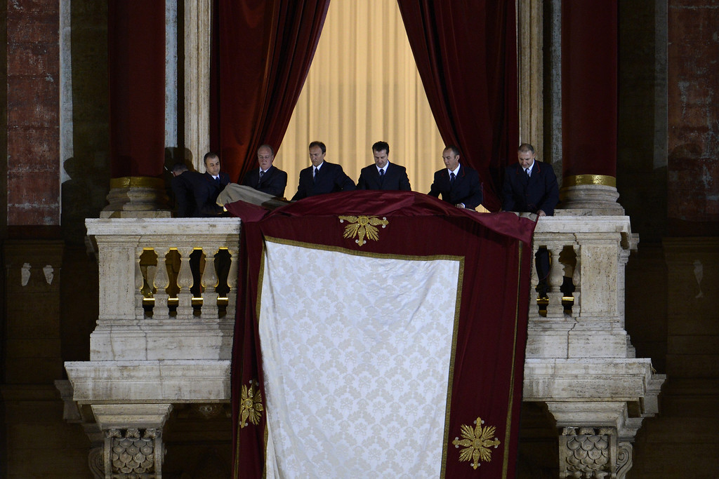 . Assistants prepare the balcony prior the arrival of the elected cardinal, Argentinian cardinal Jorge Mario Bergoglio elected Pope Francis I on March 13, 2013 from the balcony of St Peter\'s basilica at the Vatican. ANDREAS SOLARO/AFP/Getty Images