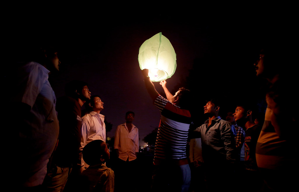 . Indians watch a sky lantern take flight during Diwali festival in New Delhi, India, Thursday, Oct. 19, 2017. The Supreme Court this year banned the sale of firecrackers in the Indian capital and neighboring areas to prevent a toxic haze after the Diwali nights that has residents hiding indoors. (AP Photo/Altaf Qadri)