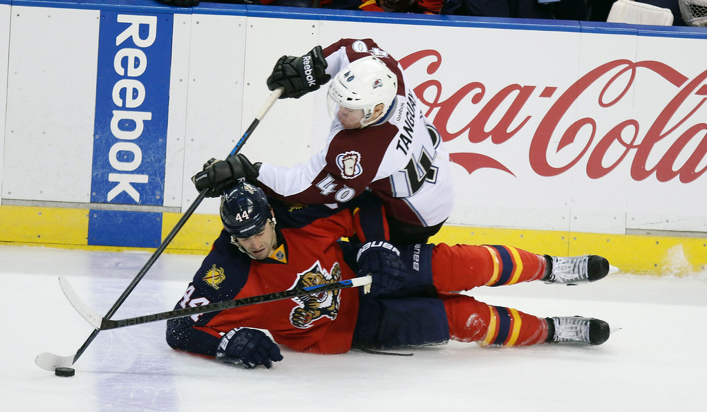 . Florida Panthers\' Erik Gudbranson (44) and Colorado Avalance\'s Alex Tanguay (40) battle for the puck during the third period of an NHL hockey game, Thursday, Jan. 15, 2015 in Sunrise, Fla. The Avalanche won 4-2. (AP Photo/J Pat Carter)