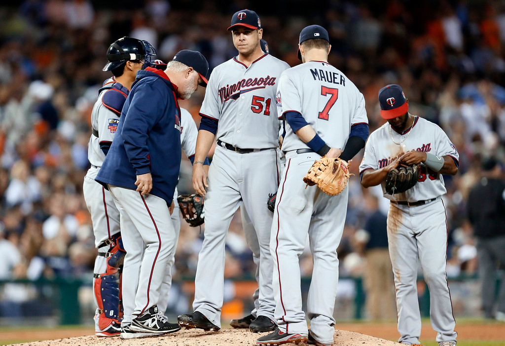 . Minnesota Twins relief pitcher Anthony Swarzak (51) is pulled by manager Ron Gardenhire in the fifth inning of a baseball game in Detroit, Friday, Sept. 26, 2014. (AP Photo/Paul Sancya)