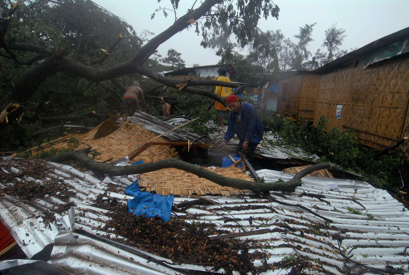 . Residents retrieve their belongings after their house was destroyed by a fallen tree caused by Typhoon Bopha in Cagayan de Oro City, southern Philippines December 4, 2012. At least 34 people, mostly soldiers, were killed after flash flood struck a military temporary command post in New Bataan, Compostela Valley, local media reported.  REUTERS/Stringer