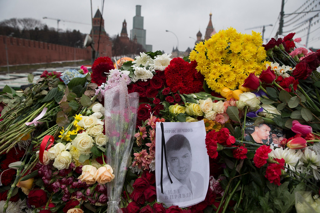 . Portraits and flowers are seen at the place where Boris Nemtsov, a charismatic Russian opposition leader and sharp critic of President Vladimir Putin, was gunned down on Friday, Feb. 27, 2015 near the Kremlin, with the Kremlin Wall is in the background in Moscow, Russia, Sunday, March 1, 2015. Russian investigators, politicians and political commentators on state television on Saturday covered much ground in looking for the reason Nemtsov was gunned down in the heart of Moscow, but they sidestepped one possibility, that he was murdered for his relentless opposition to Putin. (AP Photo/Pavel Golovkin)