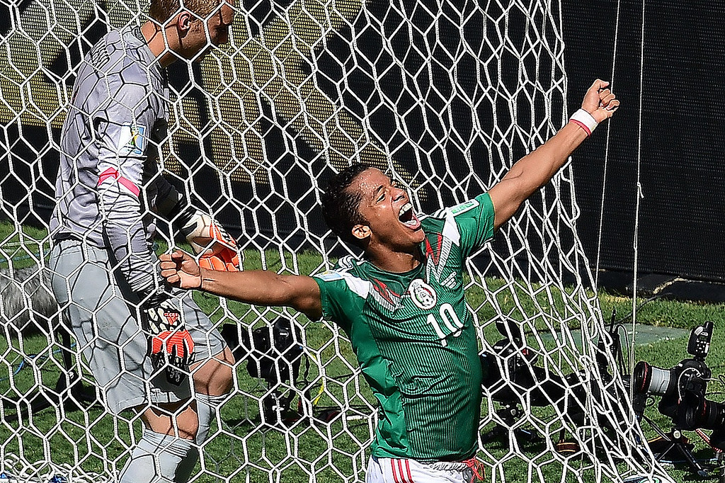 . Mexico\'s forward Giovani Dos Santos (R/10#) runs past Netherlands\' goalkeeper Jasper Cillessen as he celebrates after scoring during a Round of 16 football match between Netherlands and Mexico at Castelao Stadium in Fortaleza during the 2014 FIFA World Cup on June 29, 2014.  JAVIER SORIANO/AFP/Getty Images