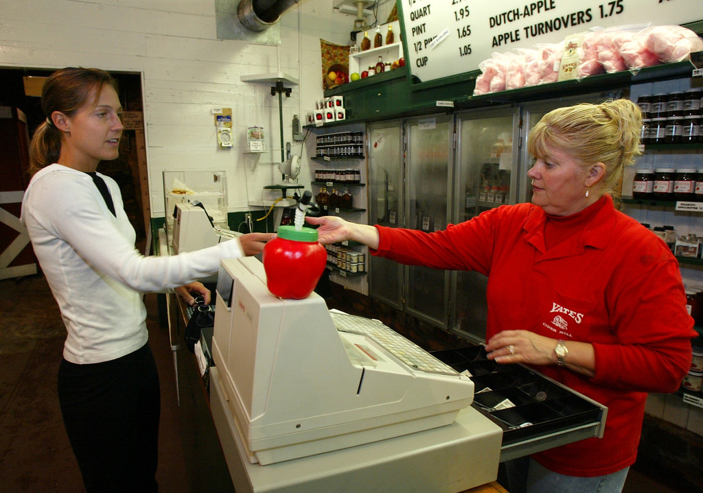 . Shelley McLaren of Rochester Hills receives change from Doris Delmotte of Shelby Township during a visit to Yates Cider Mill. Photographed Monday, September 22, 2003.