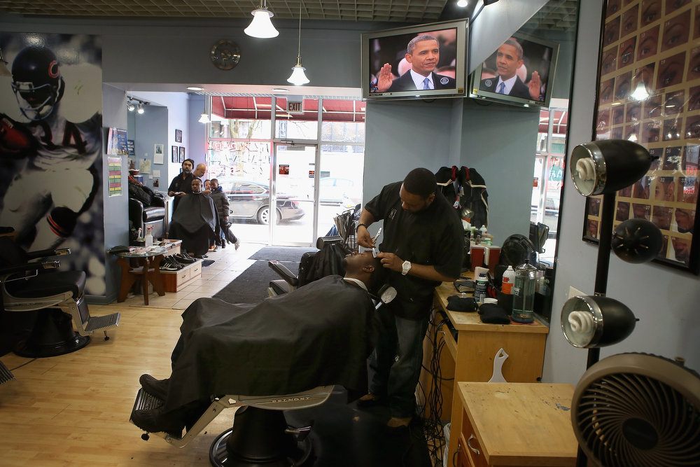 Description of . Eligio Valencia gets a shave and haircut from Essex Jemison at the Hyde Park Hair Salon while President Barack Obama takes the oath of office January 21, 2013 in Chicago, Illinois. Obama would get his hair cut at Hyde Park Hair Salon, which is near his Chicago home, before he was elected to the White House.  (Photo by Scott Olson/Getty Images)
