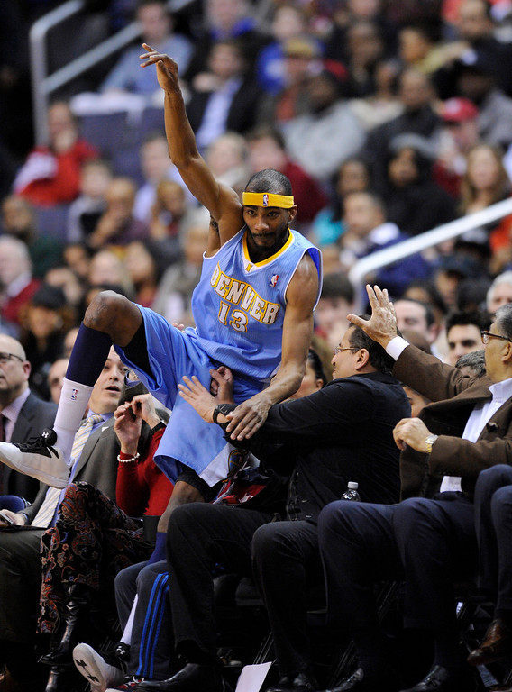 . Denver Nuggets forward Corey Brewer falls into the crowd during the first half of an NBA basketball game against the Washington Wizards, Friday, Feb. 22, 2013, in Washington. (AP Photo/Nick Wass)