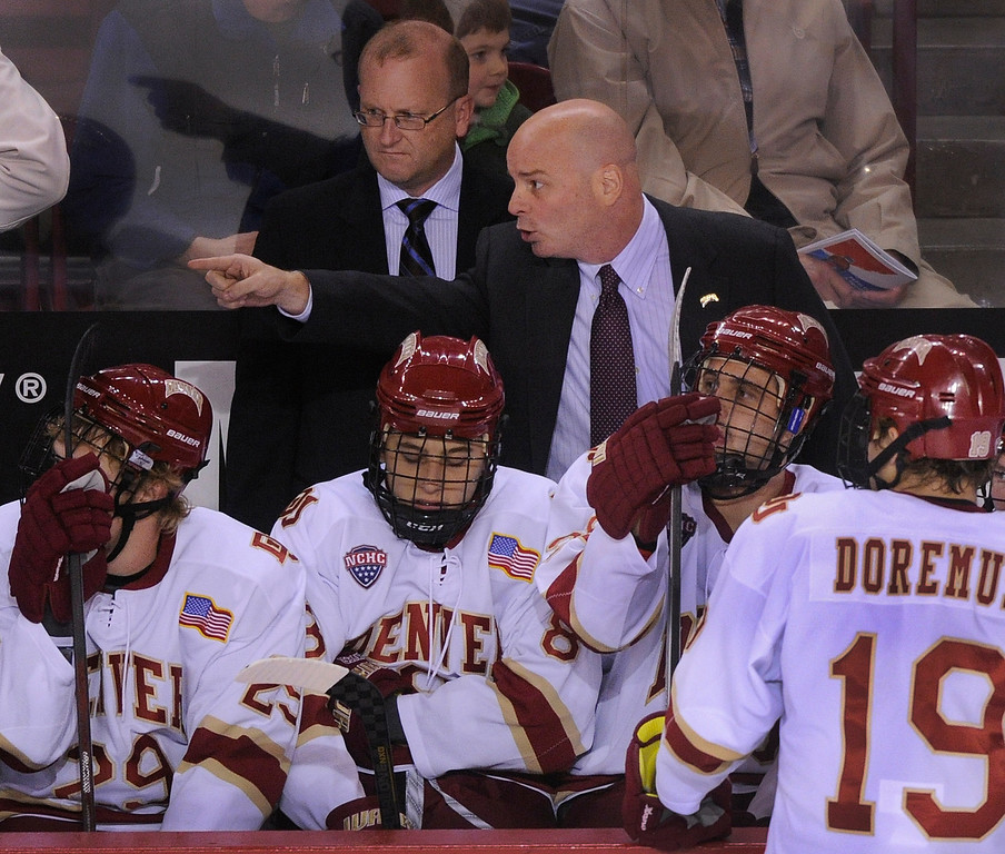 . DENVER, CO. - OCTOBER 12: Denver head coach Jim Montgomery made a point in front of associate head coach Steve Miller in the first period. The University of Denver hockey team hosted Merrimack at Magness Arena, Saturday night, October 12, 2013. Photo By Karl Gehring/The Denver Post