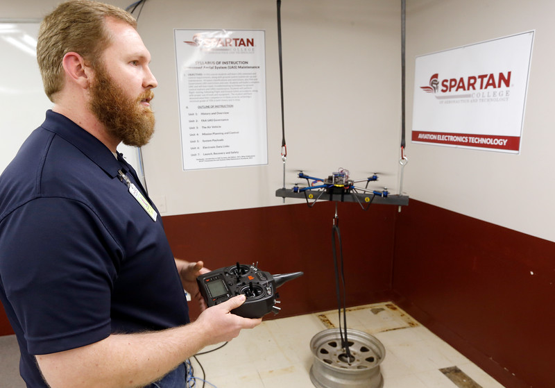 Michael Brown, Student at Spartan College of Aeronautics in Tulsa, flies a tethered Unmanned Aerial Vehicle during a press conference announcing a new curriculum centered around maintenance of the UAV's.