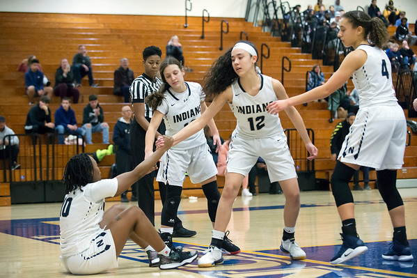 02/20/20 Wesley Bunnell | StaffrrNewington girls basketball defeated Enfield on thursday night at home in the first round of the conference tournament. Kayleigh Sanchez (12) helps Ashanti Frazier (10) off the floor after being knocked down on a shot attempt.