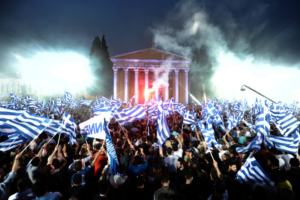 Description of . Supporters of Leader of the Greek conservative party New Democracy Antonis Samaras wave flags during a pre-election speech in Athens on May 3, 2012. Crunch elections in Greece on May 6 may not produce a government with a strong enough mandate to push through yet more austerity cuts to satisfy Athens' international creditors. Sunday's election is expected to see Greek voters, many of them fed up with grinding austerity drives, vote for parties that say they would scrap deals with the EU and IMF. AFP PHOTO / ARIS MESSINIS/AFP/Getty Images
