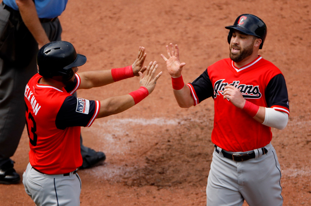 . Cleveland Indians\' Melky Cabrera, left, and Jason Kipnis celebrate after scoring on a two-run single by Francisco Lindor during the sixth inning of a baseball game against the Kansas City Royals, Sunday, Aug. 26, 2018, in Kansas City, Mo. (AP Photo/Charlie Riedel)